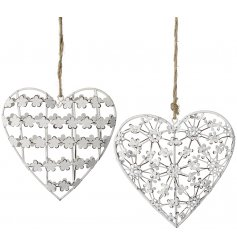 An assortment of 2 hanging metal heart decorations, each with a delicate floral design and jute string hanger.