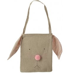 A natural fabric bunny bag with pink polka dot ears and a pom pom nose.