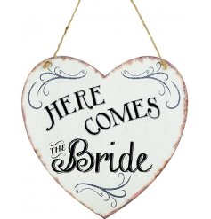 A shabby chic style metal heart shaped sign reading HERE COMES THE BRIDE.
