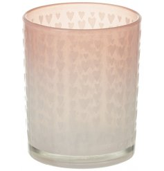A chic glass t-light holder with small decorative love hearts. A charming gift item and interior accessory.