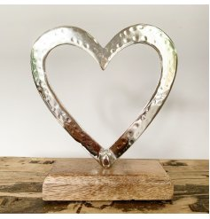 A stylish and chic large aluminium open heart decoration on a mango wooden base for interior display.