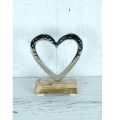 A beautifully hand finished open heart decoration set upon a mango wood base.