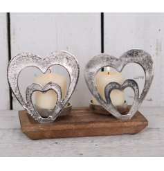 A chic decorative accessory for the home. This double candle holder has a chunky wooden base and silver aluminium hearts