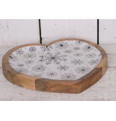 A chic heart shaped tray with an enamel surface with snowflakes.