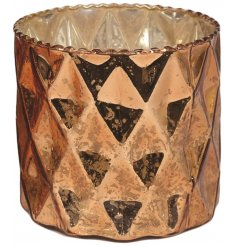 A chic glass candle holder with a geometric design and aged antique finish.