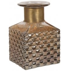 A vintage style glass bottle. A square design with a decorative surface pattern and gold bottle neck.