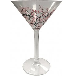 A beautifully designed martini cocktail glass with a pink and white Japanese blossom floral design.