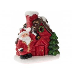 A charming festive house with a Santa ornament and LED lights. A traditional decoration for the home.