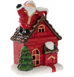 A charming red festive house with Santa on the roof. A traditional Christmas ornament with light up feature.