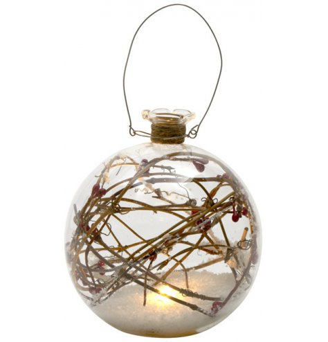 A bottle top shaped bauble filled with artificial snow, red berries and twig branches, and twinkling LED lights.