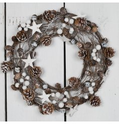 A beautifully decorated woven wreath set with a scatter of twigs, pinecones, stars, berries and bells.