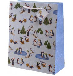 a glossy gift bag covered with wintery penguins enjoying the snow