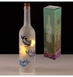 A beautifully illuminated glass bottle featuring a frosted decal, magical mermaid print and added cork top