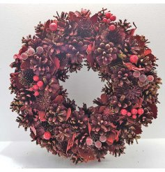 A beautiful berry red Christmas wreath, filled with pinecones and rich red frosted berries.
