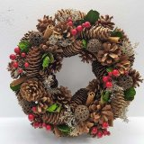 A beautiful and unique berry wreath, adorned with cinnamon sticks, red berries and dried flowers.