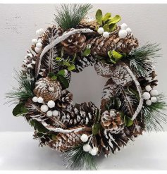 A natural leafy green wreath with snow dusted pinecones, berries and foliage.