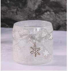 A stunning frosted glass candle holder with a hanging snowflake and snowflake ribbon.
