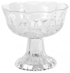 A clear glass bowl featuring a long footed base and added embossed patterns