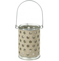 A chic glass lantern with a hessian snowflake design wrap, revealing the warming winter glow of a t-light.