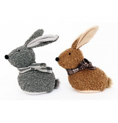 An assortment of 2 grey and brown fabric doorstops, each with a check scarf and fluffy pom pom tail.