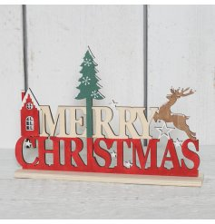 A charming wooden Merry Christmas sign with a prancing reindeer, nordic house and festive tree.