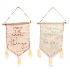 An assortment of pink an blue scripted fabric bunting featuring added tassels and prints