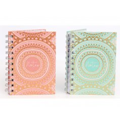 An assortment of pink an blue toned hardback notebooks featuring charming gold patterns and decals