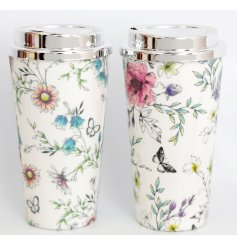 An assortment of 2 floral design travel mugs, with whimsical flowers and butterflies.