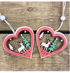 A set of 2 hanging wooden heart decorations with festive scene centres and added red and green tones