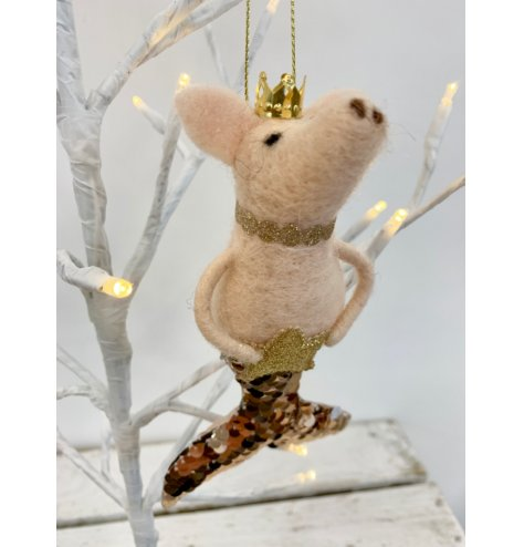 A hanging felt pink pig with a sequin mermaid tail and gold details in the form of a crown and star.