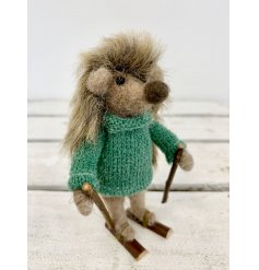 A cute little woollen hedgehog with added faux fur spikes and an adorable green knitted jumper decal