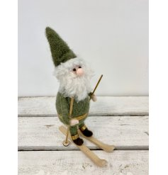 A charming little woollen Santa decoration dressed in a green outfit and placed on skis