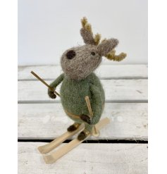 A charming little woollen Reindeer decoration dressed in a green outfit and placed on skis