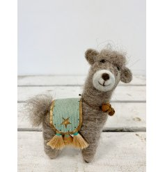 A cute little woollen Llama with an added bell necklace and green saddle