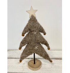 A fuzzy woollen Christmas tree in a beige tone, decorated with little rusted bells and a wooden star on top