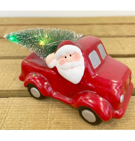 A jolly Santa in his truck, heading home for Christmas complete with festive light up Christmas tree.