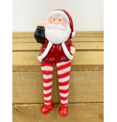 A sweet little shelf sitting ceramic Santa with long dangly legs