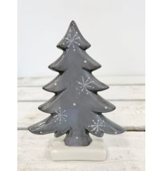 A small ceramic tree decoration set with a distressed grey tone and added snowflake decals