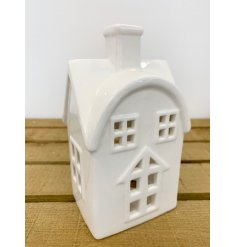 A simple white toned ceramic house decoration with an added tlight holder space