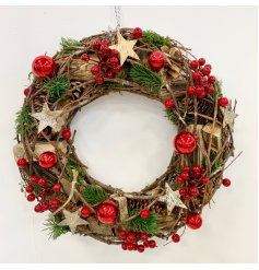 A charmingly clustered Christmas wreath decorated with woodland inspired foliage and scattered with added red accents