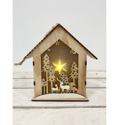 A natural toned wooden house decoration complete with a cut out woodland scene and warm glowing LED surround