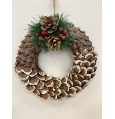 A large round wreath set with a pinecone ridge decal, pine branch foliage and added red berries