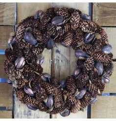 A beautifully decorated round wreath decorated with a cluster of sized pinecones and shells