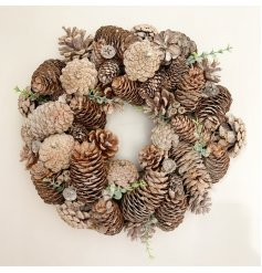 A large cluster of natural toned pinecones build up this beautifully decorated round wreath