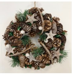 this wreath is made up of frosted pinecones, berries, stars and pompoms then beautifully kept together with a woven twig
