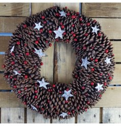 A large round oasis built up of chunky pinecones, covered with a flurry of stars and red berries