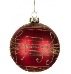 A festive red toned glass bauble featuring a gold glitter musical note decal