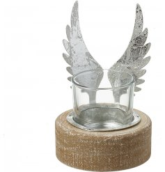 A shabby and chic themed candle holder with a wooden base and distressed silver wing decal