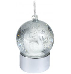A beautifully elegant hanging glass snow globe featuring a glittery flurry and white swan centre scene