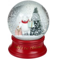 A magical snow globe decorated with 'Baby's First Christmas' script.